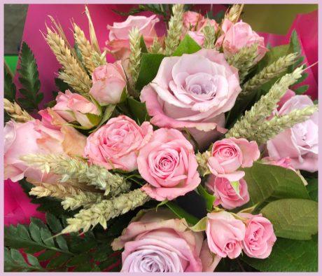 Bouquet rond de roses roses, blé et feuillage